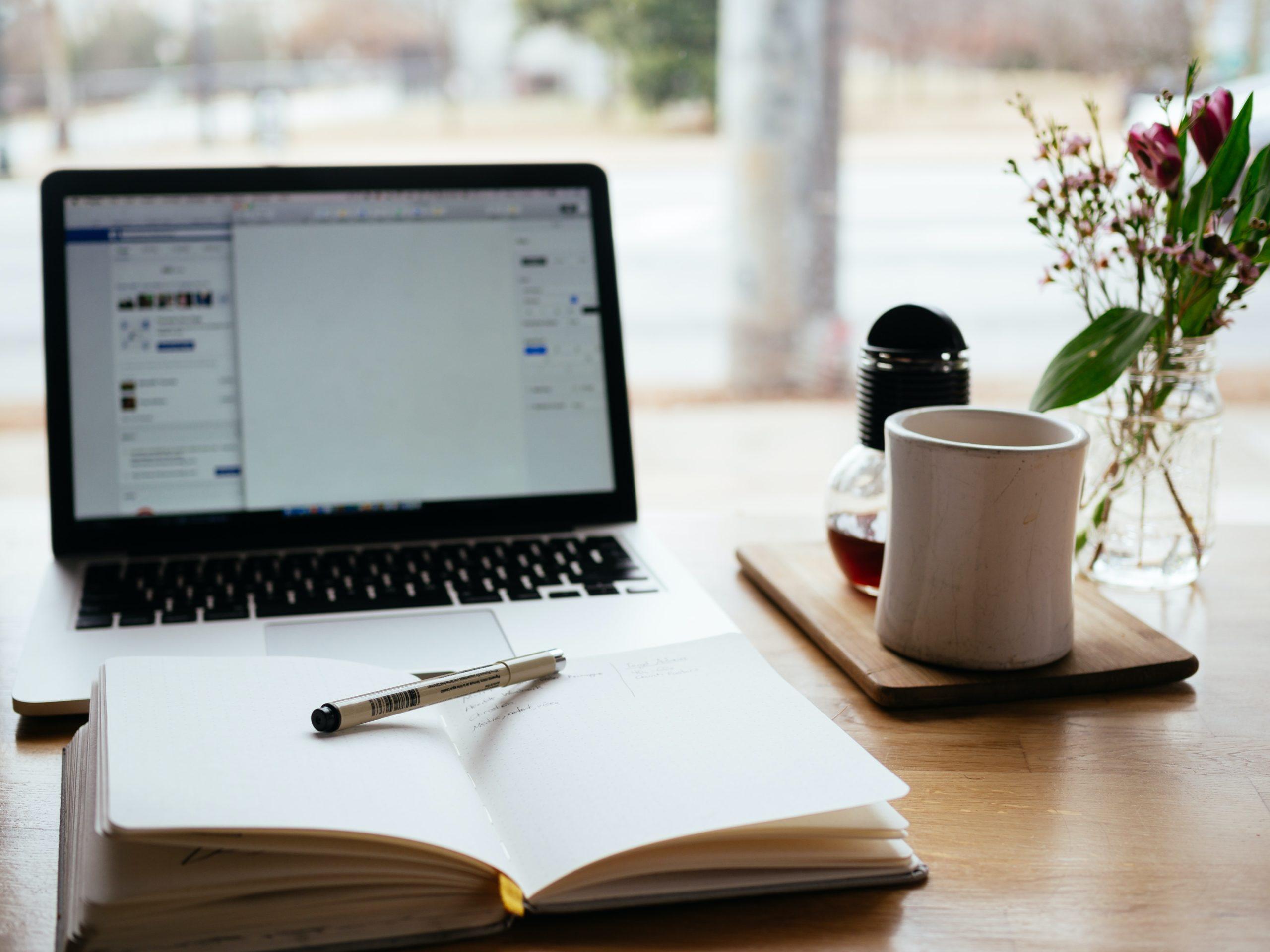 PC, notatbok, og kaffekopp er alt du trenger i hverdagen.