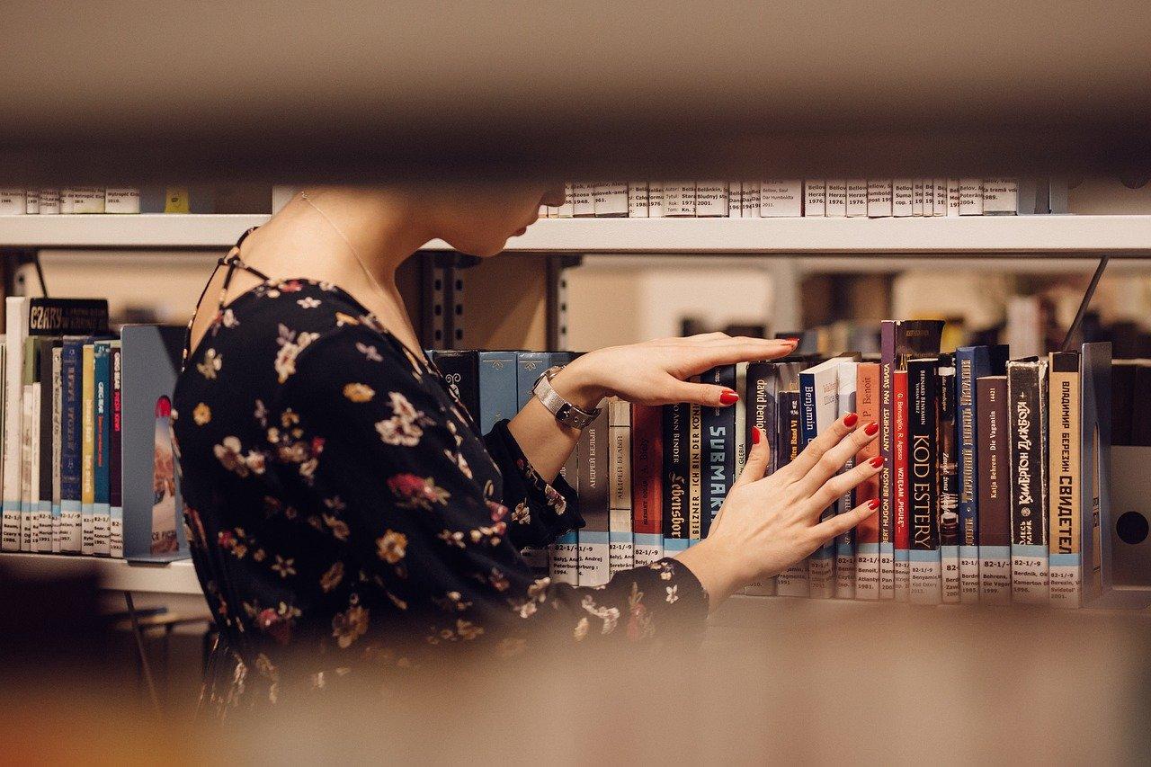 Akademisk tekst er å finne hos de mange bøkene i et bibliotek.