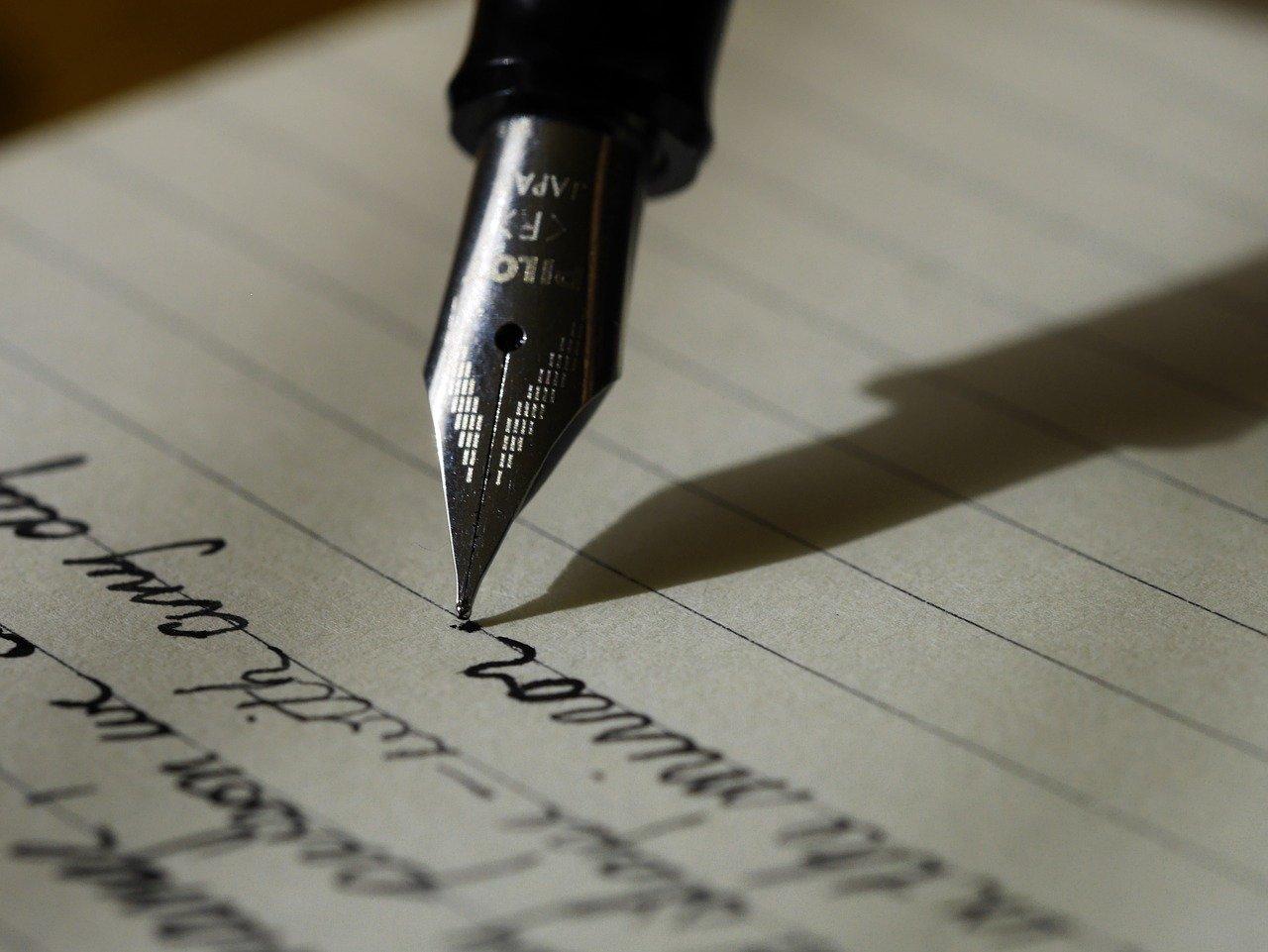 Penn med blekk som skriver på ark