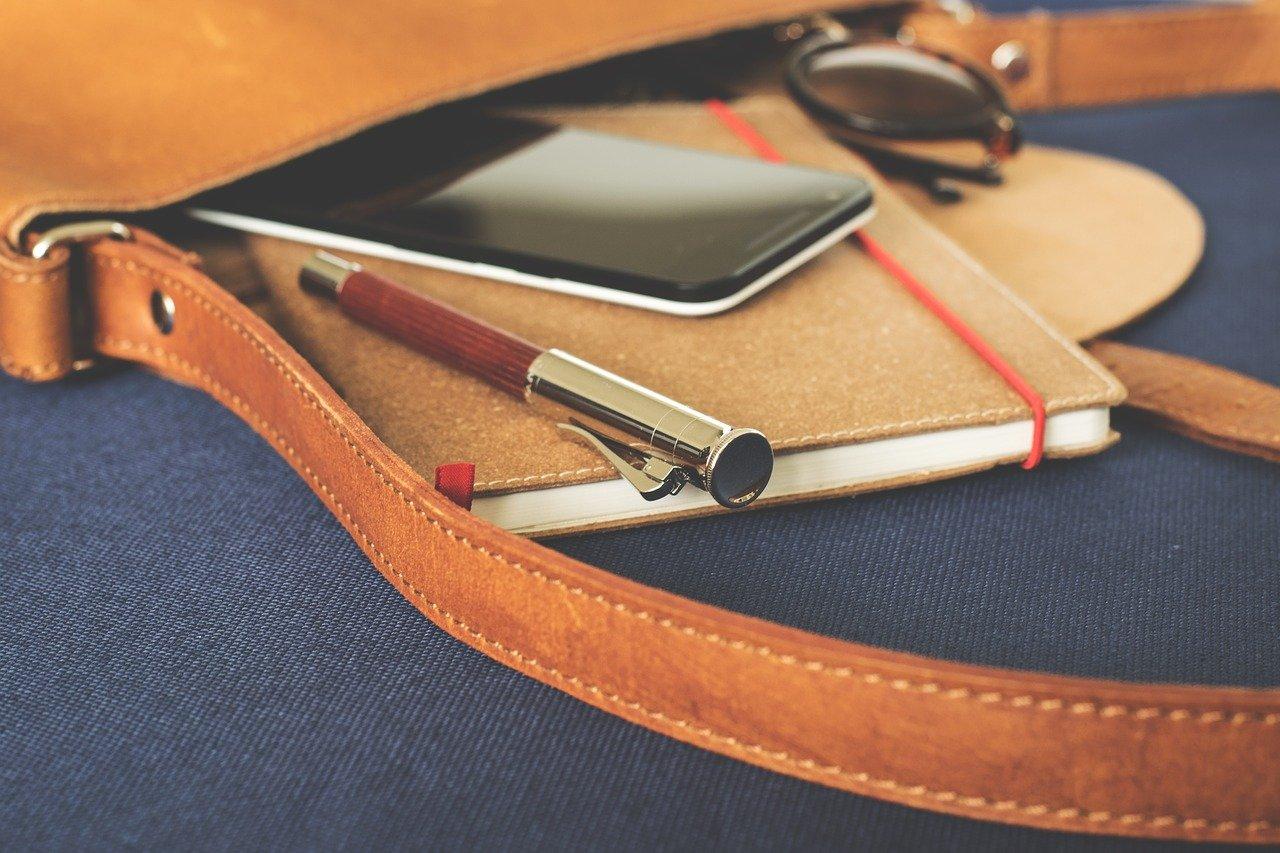 Notisblokk, penn og mobil i veske