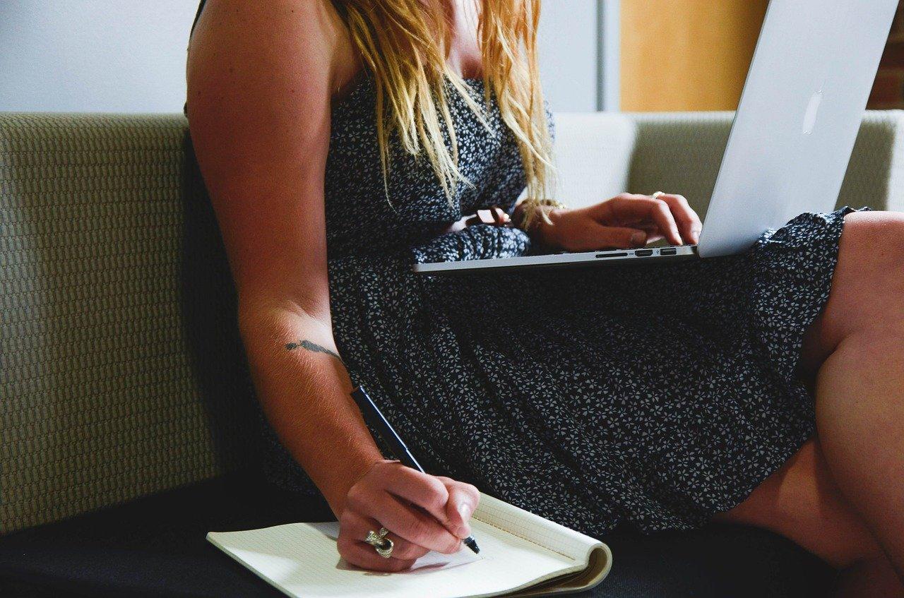 Ei dame som skriver en bryllupstale med datamaskinen på fanget