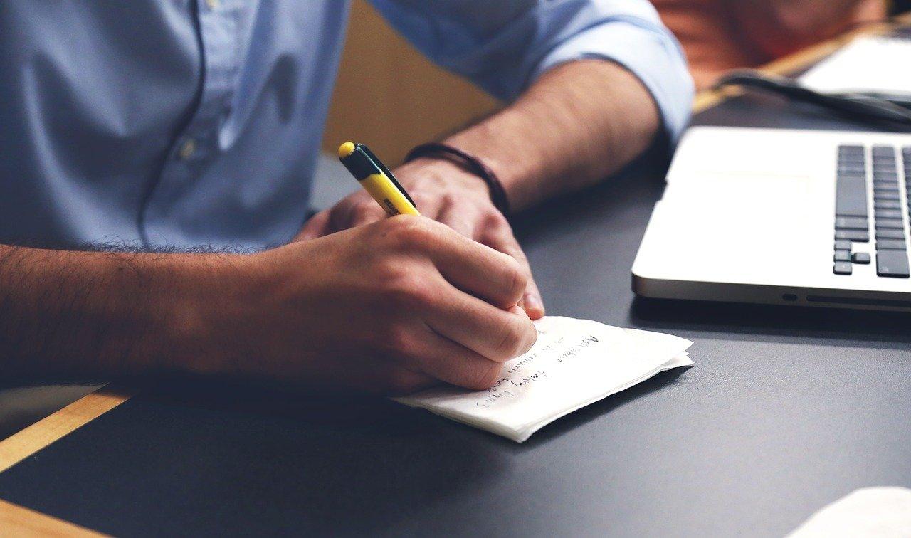 En mann som skriver forslag til tale på notatblokk